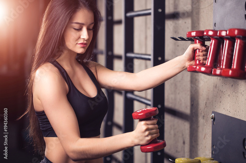 woman strength training lifting dumbbell weights getting ready for exercise workout