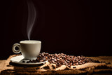 Cup of coffee with smoke and coffee beans on black background - 194363952