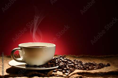 Papiers peints Café en grains Cup of coffee with smoke and coffee beans on reddish brown background