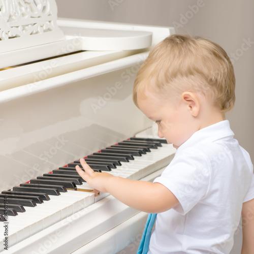 Fototapeta Little boy playing the piano