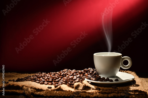 Fototapeta Cup of coffee with smoke and coffee beans on reddish brown background