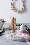 Easter  festive table setting with Easter bunny cookies, quail eggs  and chicken egg, green  leaf sprigs of eucalyptus. On a gray concrete background. Holiday celebration decorations.