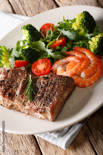 Aluminium Steakhouse Delicious juicy barbequed steak and prawns with vegetable salad closeup. Surf and Turf style. horizontal