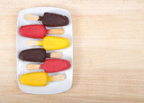 Colorful candy covered cake popsicles on a white plate alternating flavors and direction of cake pops, laying on a light wood table. Fun birthday party treats, easy to hold for small hands.