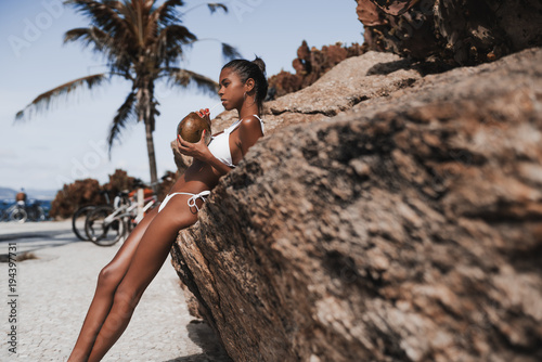 Serious young hottie black female is drinking fresh coco water while leaning on the cliff with beach and palms in the background; sexy Brazilian girl in swimsuit is slaking her thirst near the rock