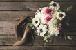 flat lay with bridal shoes and beautiful bouquet on wooden tabletop