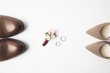 top view of pairs of bridal and grooms shoes, corsage and wedding rings isolated on white