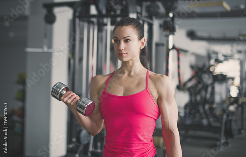 Aluminium Fitness Strong bodybuilder biceps workout with dumbbell in gym