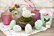 easter decoration with porcelain bird in nest and eggs