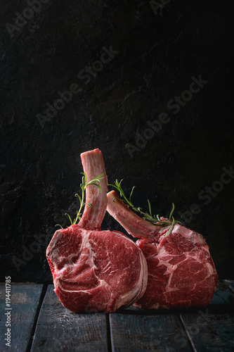 Aluminium Steakhouse Raw uncooked black angus beef tomahawk steaks on bones served with rosemary over dark wooden plank table. Rustic style. Close up