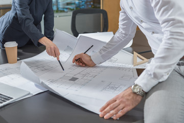cropped shot of stylish architects working with building plans together at office