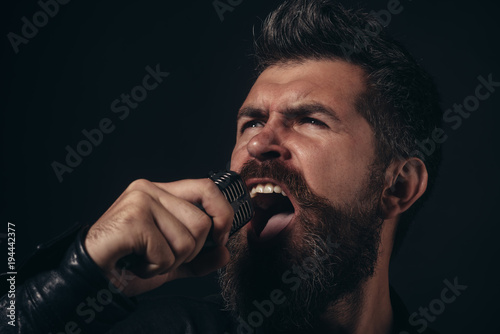 Fototapeta Handsome man singing to microphone. Emotional portrait attractive guy with beard. Male vocalist singing into microphone. Rock-singer. Closeup.
