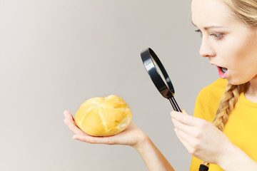 Shocked woman magnifying bun bread roll