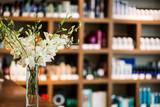 цветы в вазе на фоне стеллажа с косметикой в салоне красоты