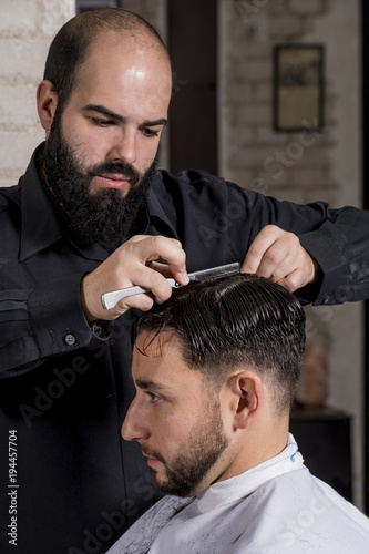 Hairdresser cutting a client's hair with a razor © fresnel6