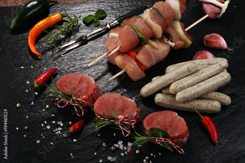 Selection of marinaded meat for bbq grilling with herbs on table - 194461529