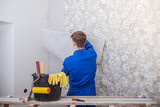 Young worker making repair in room, wallpapering on wall  - 194485777