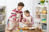 mother and daughter mother and daughter break egg into flour, home kitchen interior, healthy food concept - 194486746