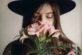 stylish hipster girl in hat holding pink flowers and petals on sweater growing. boho woman with beautiful alstroemeria in hands, smelling flower. creative sensual female portrait. calm face - 194493724