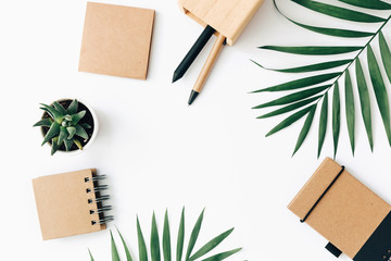 Minimal Office desk table with stationery set, supplies and palm leaves. Top view with copy space, creative flat lay.