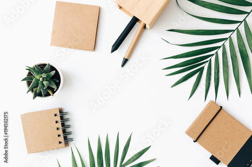 Fototapeta Minimal Office desk table with stationery set, supplies and palm leaves. Top view with copy space, creative flat lay.