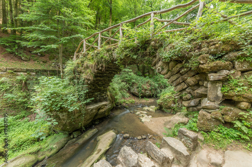 Fotobehang Bergrivier Stone medieval bridge crossing a stream inside of a wood forest