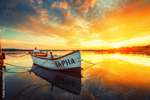 Fishing Boat on Varna lake with a reflection in the water at sunset