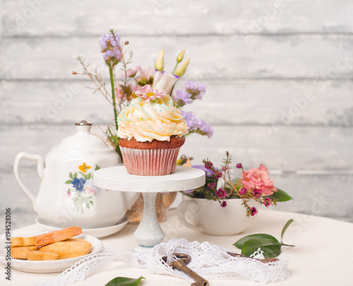Cup cakes with cream cheese topping on beautiful wooden cake stand with flowers