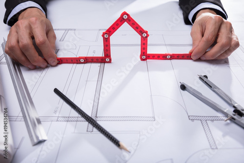 Wall mural Architect Holding House Made With Red Measuring Tape