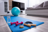 Skipping Rope And Pink Dumbbells On Exercise Mat