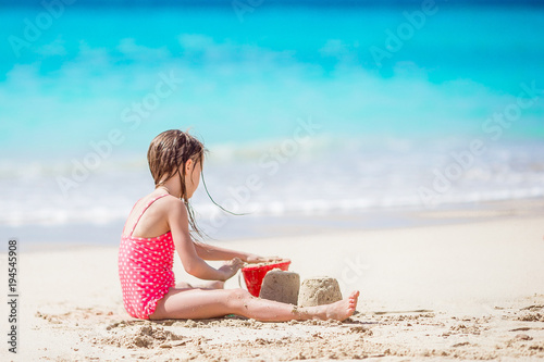 Fotobehang Turkoois Adorable little girl playing with beach toys on white tropial beach