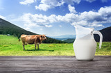Jug of milk against background of cow and mountain pasture - 194553714