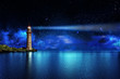 Leinwanddruck Bild - Safety and hope concept, a lighthouse on a tropical island on the ocean with a beam of light in the night sky with stars