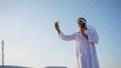 Fotobehang Abu Dhabi Happy, handsome guy, emirate and tourist, conducts dialogue through Internet with help of device, waves hand and smiles at camera of smartphone, shows beautiful views and sights of large sandy desert