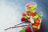 Detox water with strawberry and cucumber in two glasses on dark background. Copyspace.