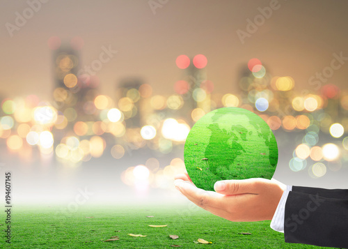World environment day concept: Businessman hand holding earth globe of grass over blurred city background
