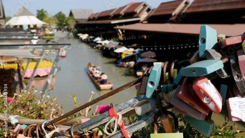 Pattaya Floating Market. Small Tourist Wooden Boat with the Chinese are moving along the water. View through the locks on the bridge. Old Thai style and Vintage Market of Thailand, Asia