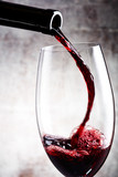 Pouring red wine into the glass against wooden background - 194619302