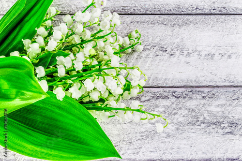 Fotobehang Lelietjes van dalen lily of the valley flowers on wooden background. Happy Easter and spring greeting card. Postcard, cover and spring border with copy space.