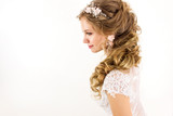 young blonde girl in a white wedding dress and jewelry in hairstyle  with big curls smiling like angel on a white wall background portrait