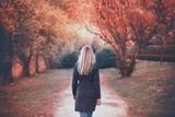 Woman walkBlonde woman in blue elegant coat walks in the sunny autumn season park. Selective focus used.s in autumn park - 194636905