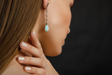 красивая молодая женщина стоит спиной к камере и положила пальцы руки на шею, а в ухе у нее красивая сережка с голубым камнем