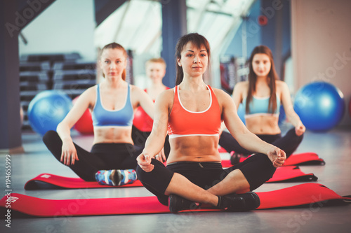 Aluminium School de yoga Sporty people sitting on exercise mats at a bright fitness studio. Sporty girls
