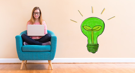 Eco Light Bulb with young woman using her laptop in a chair