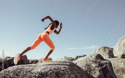 Female runner running over big rocks