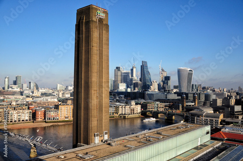 Deurstickers Londen Tate modern famous chimney with the business district of London in the background. Typical brown brick walls building and modern architecture. Clear sky on sunny day