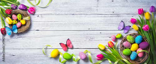 Easter background. Colorful spring tulips with butterflies and painted eggs - 194706125