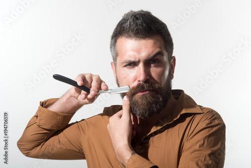 Fototapeta Bearded man with long beard, brutal, caucasian hipster with beard and moustache, holds dangerous razor near face. Stylish hairdresser with dangerous razor for shaving in studio.