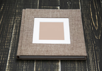 Closeup top view of family photo album isolated on brown wooden background. Horizontal flatlay photography.