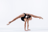 Young gymnast girl stretching and training - 194714380